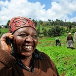 A Kenyan farmer uses a mobile phone in the field. Photo by Neil Palmer (CIAT)